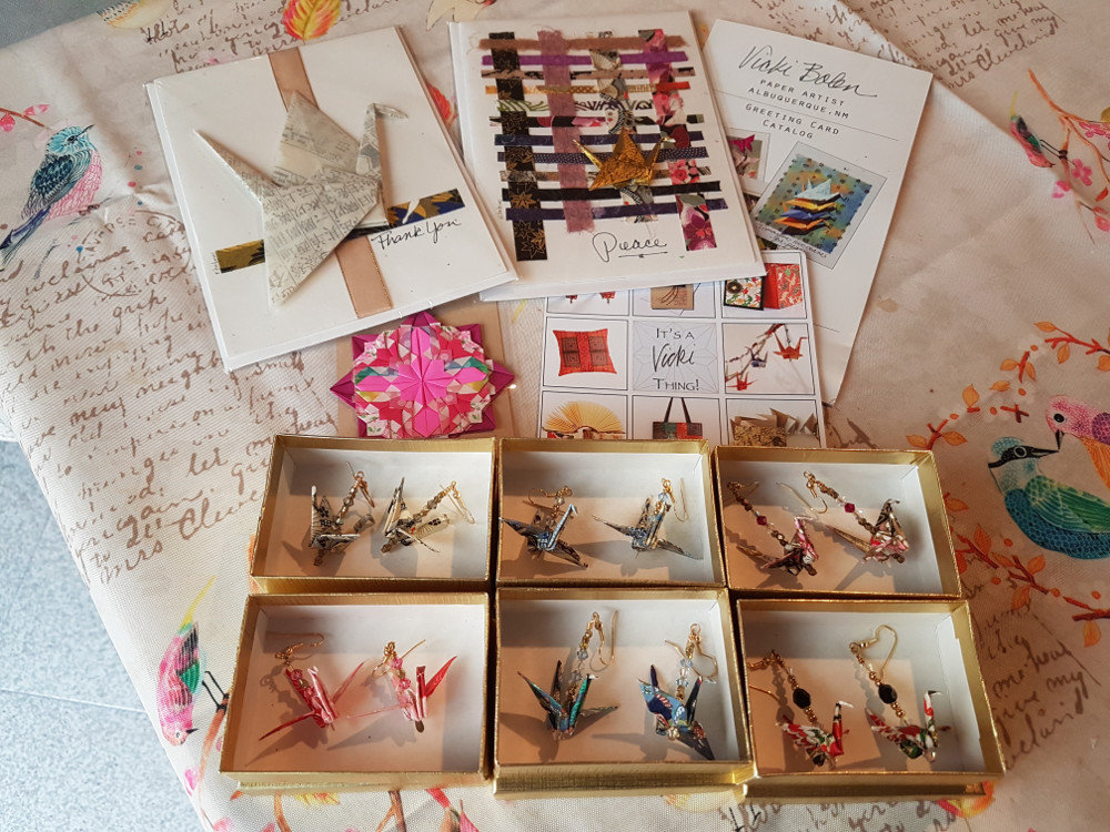 6 boxes with handmade origami earrings, 2 handmade origami greeting cards, and an origami magnet