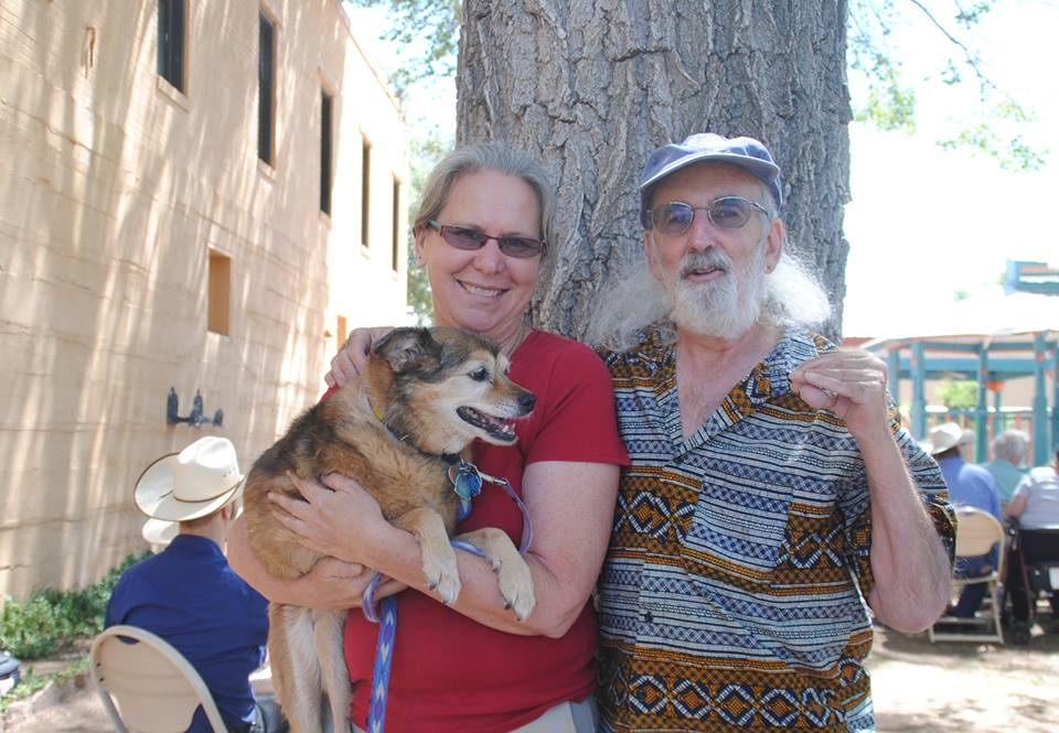 Vicki Bolen and Richard Wolfson holding dog outdoors
