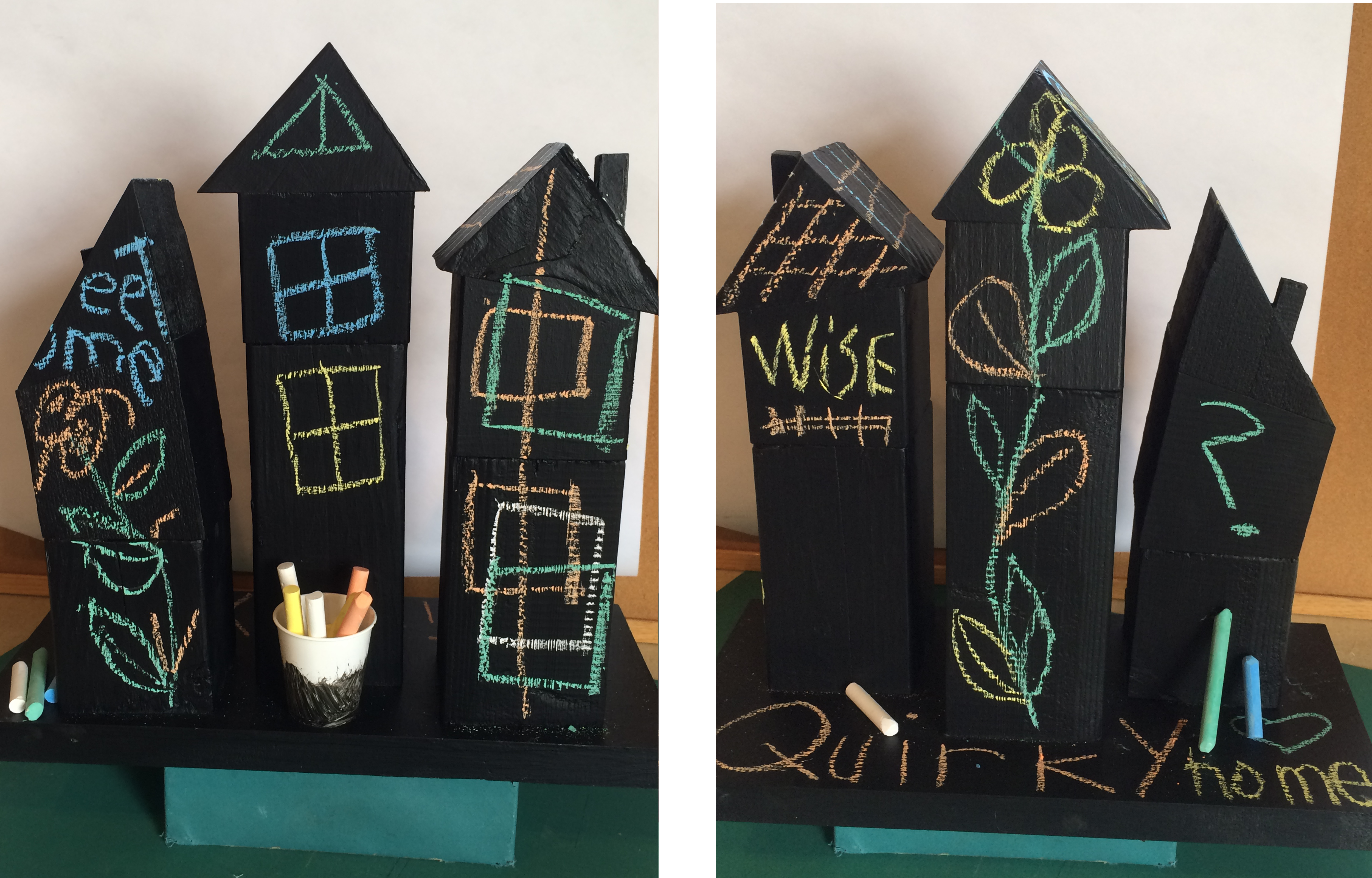 Three quirky wooden houses mounted on a board and painted with chalk board paint.
